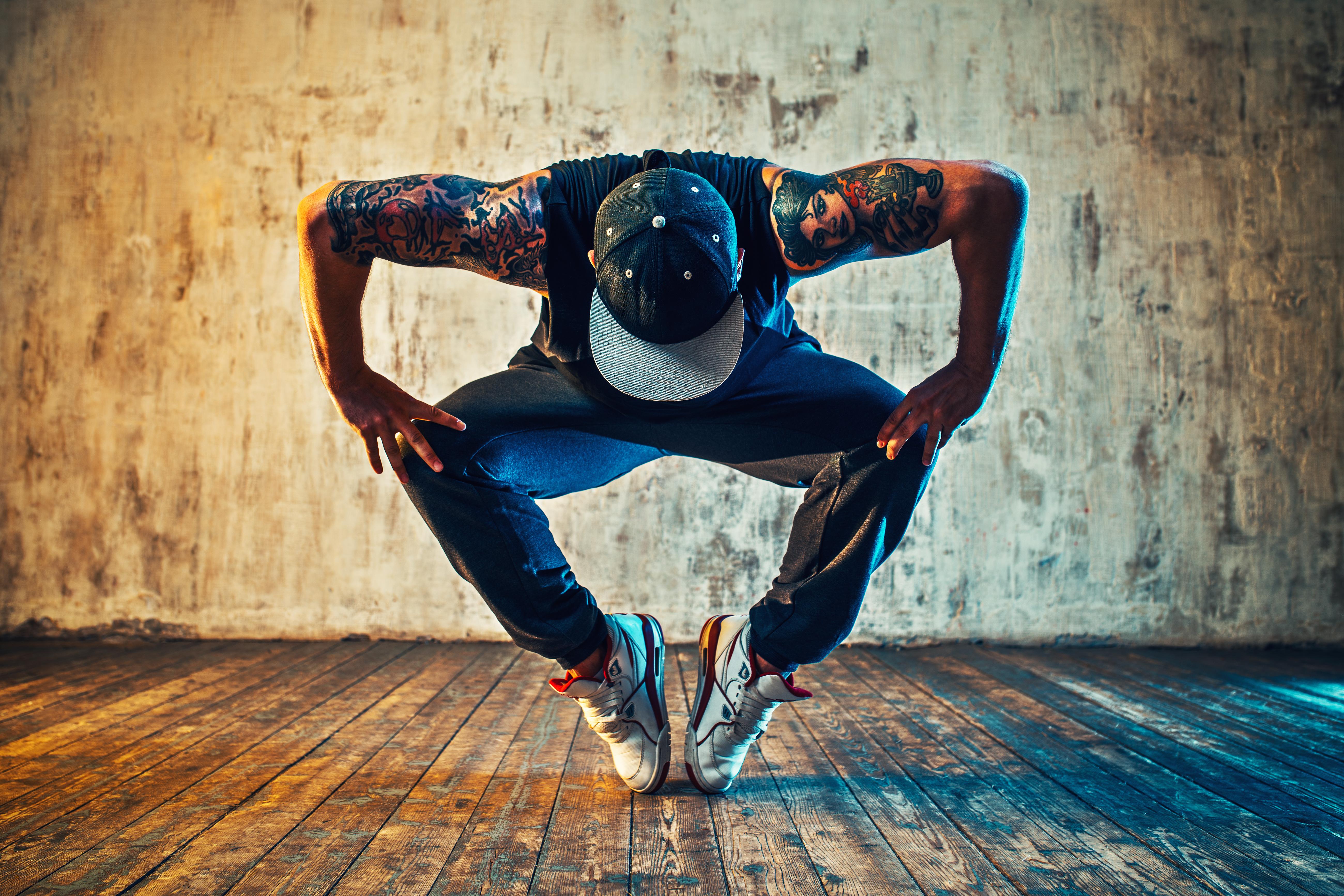 Young man break dancing on wall backgrou