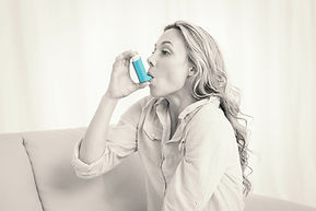 Woman using her inhaler to control asthma symptoms