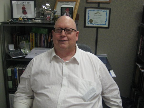 Image of a bald man, Terry Oakley, sitting at a desk.