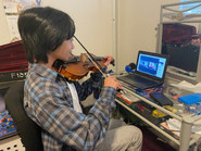 A violin student from California receiving an online lesson from high school senior Maddux Madayag