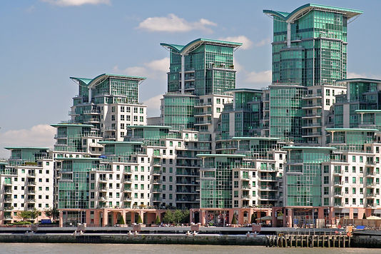 St. George Wharf is a large, mixed-use riverside development occupying an 8-acre brownfield site adjacent to Vauxhall Bridge in London. The residential part of the scheme comprises five towers rising in steps to up to 22 storeys, over sailed with 'gull-wing' roofs. The striking prow shaped forms are designed to maximise views of the River Thames and to provide deep terraces for the penthouse accommodation.  There are a number of on-site facilities available including shops, cafes and bistros situated around the piazza. The development's distinctive silhouette ensures the buildings are one of the Thames' skyline's more recognisable features.     Significantly, it has been widely acclaimed as a model modern method of construction and it is a demonstration project under the Government's Constructing Excellence programme. The exterior is a mixture of sea-green glass curtain walling with reconstructed stone finished precast concrete wall cladding panels and structural balcony units.     The developer St George (South London) Plc, part of Berkeley Homes Group, with architect Broadway Malyan created a long term working partnership with The Marble Mosaic Co Ltd at an early stage of this residential project to give supply chain security and guaranteed quality control. This early involvement also allowed the incorporation of additional features into the off-site fabrication process.     Precast concrete was chosen for the external wall cladding for its well-known advantages of low-maintenance, high quality finish and precision of construction. The size and proportion of the panels were carefully detailed, in particular to provide drainage and run-off for rainwater, avoiding staining. The panels on the upper floors match the appearance of Portland stone while on the two lowest floors the panels match the appearance of pink sandstone. This gives visual strength to the base of the building and echoes the colour of the small-scale red-brick buildings in the vicinity.