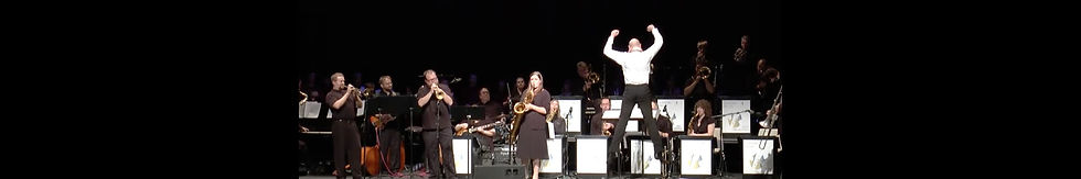 Special guest Andrew Neesley jumps in the air while conducting the orchestra