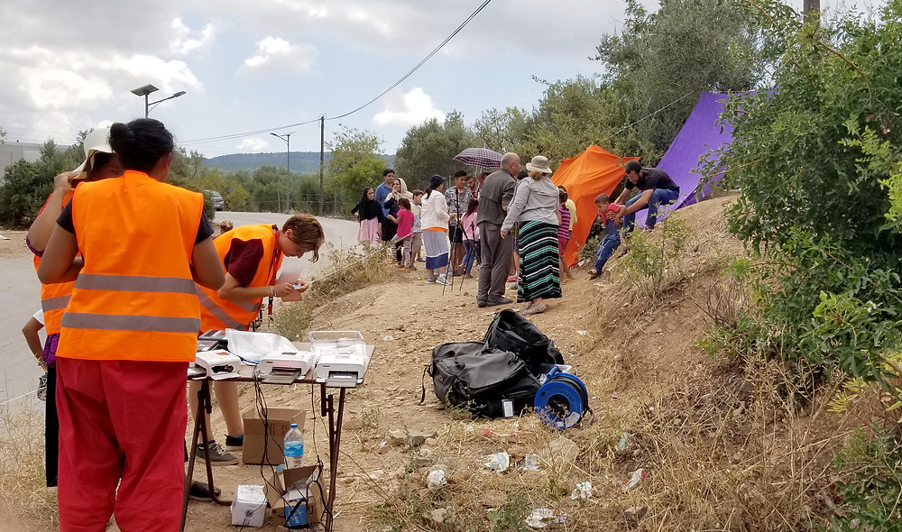 Outside the Vial Refugee Camp in Chios, Greece, we set up our makeshift portrait studio in a barren field across from the main gates of the camp. Staging areas were outlined with a spool of string to manage the crowds and serve people as quickly and efficiently as possible. July, 2018. (Photo by Alexander Huang-Menders)