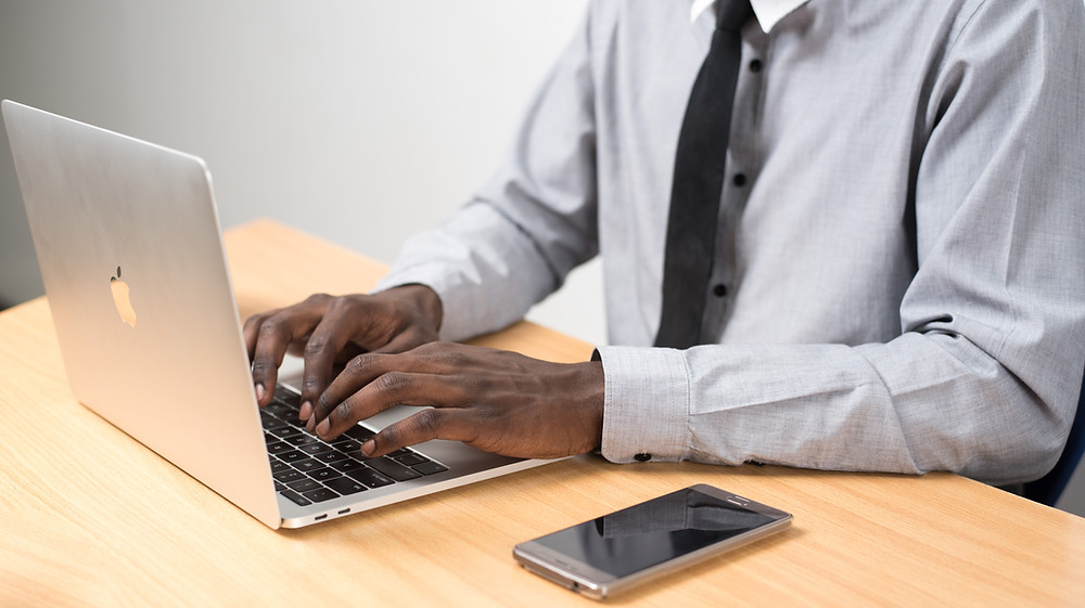 Man working at this laptop with mobile phone