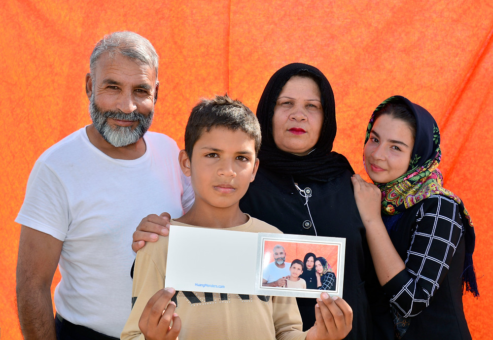 The Power of Faces has distributed thousands of printed portraits to displaced individuals in Greece, Turkey, Mexico, and Bangladesh. This family was being detained at the Vial Refugee Camp in Chios, Greece. July, 2017. (Photo from The Power of Faces)