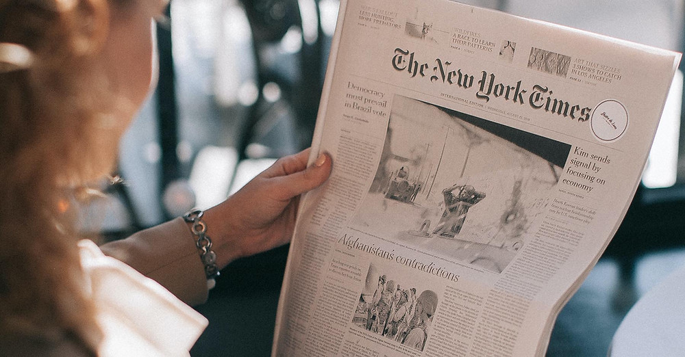 A woman reads The New York Times