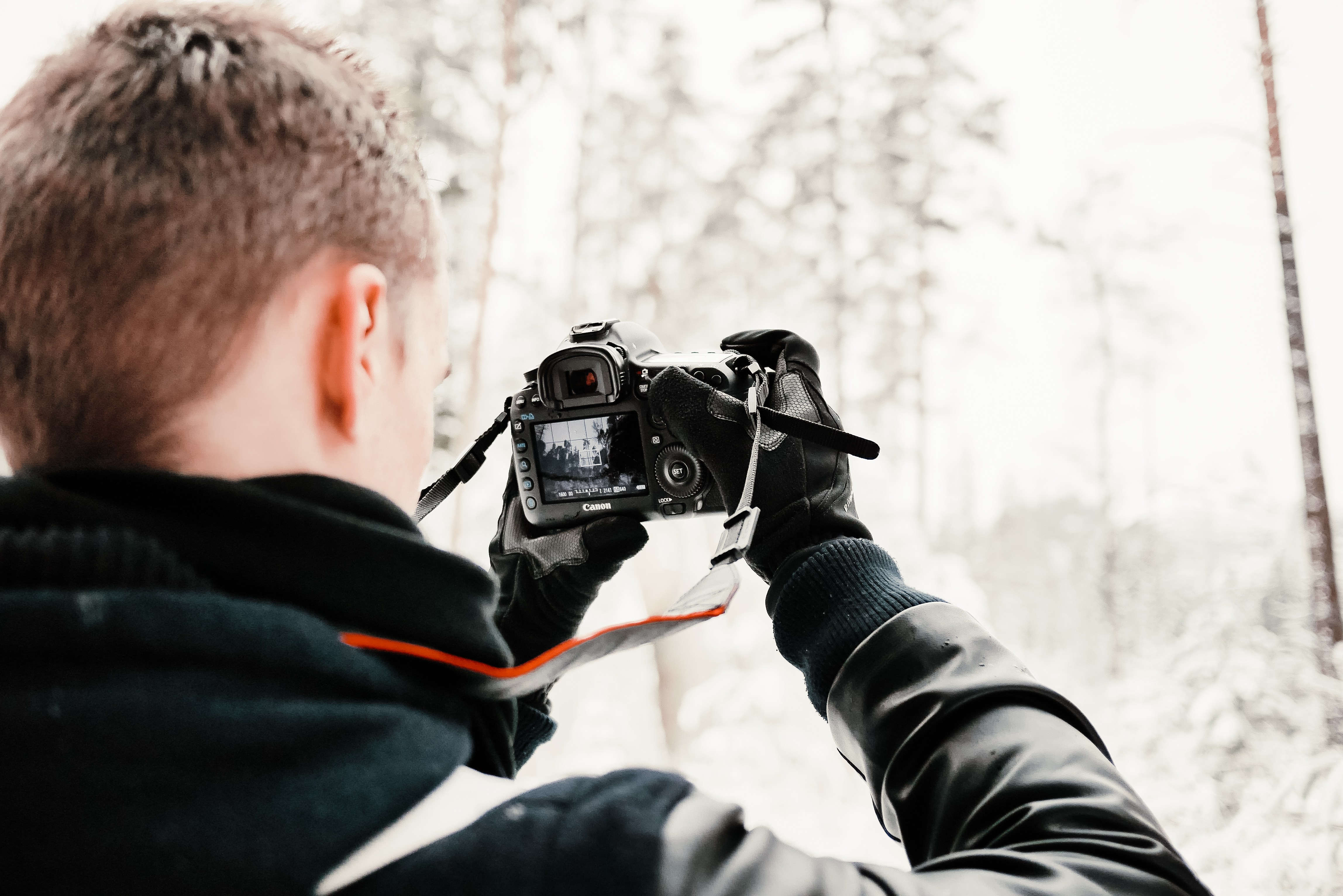 photographer-in-snowy-forest-taking-wint