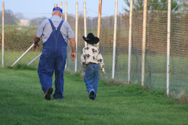 Picture of a farmer and his young grandson, checking the property.