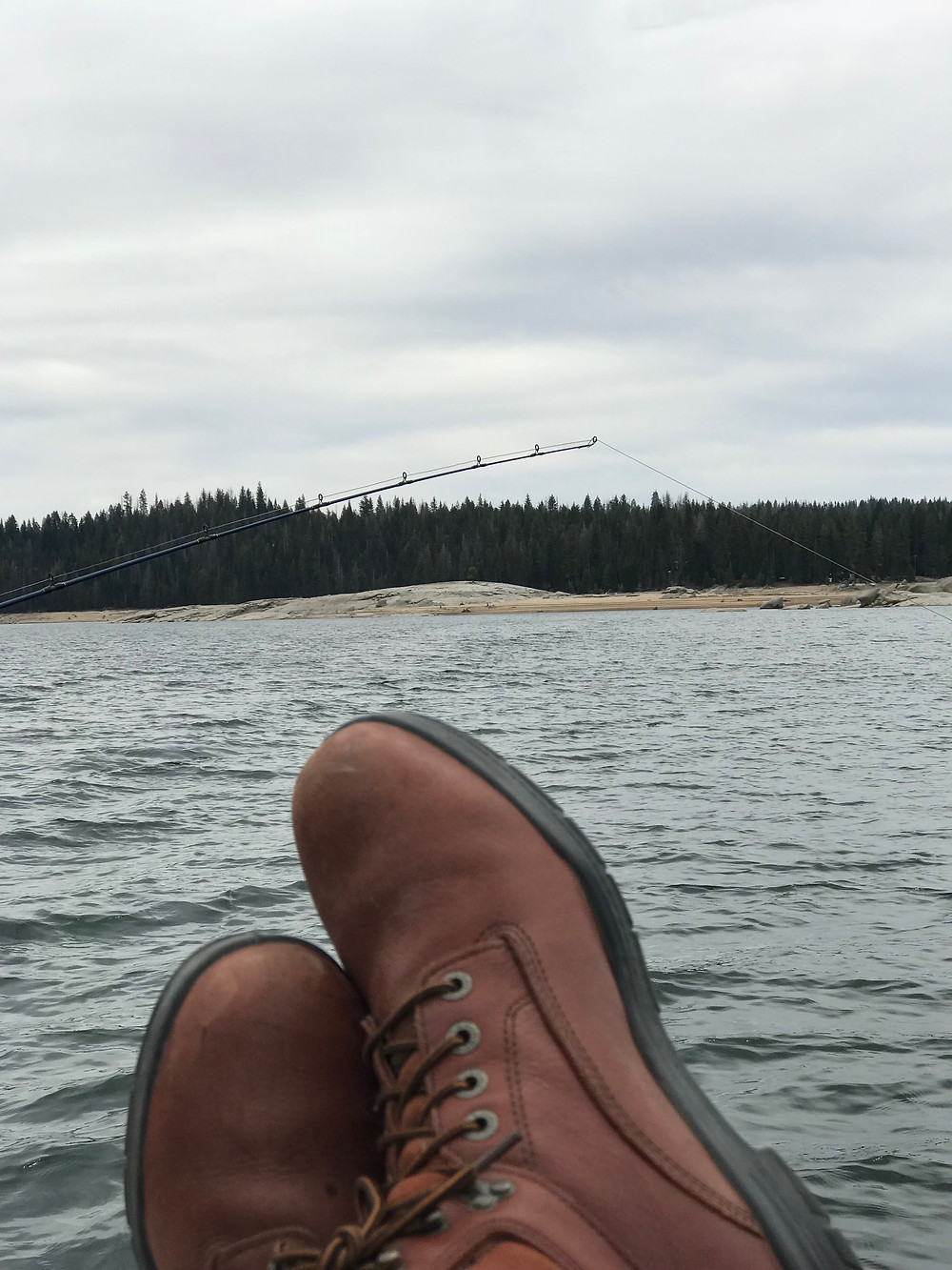 """Image of owner Sean Glover's shoes as he fishes during the brief """"off season"""" for tree nut pest prevention."""