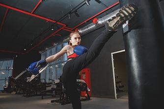 kickboxing-woman-punching-kicking-bag-at
