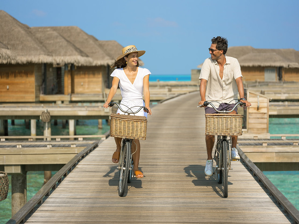 Um casal passeando de bicicleta no Vakkaru Maldives