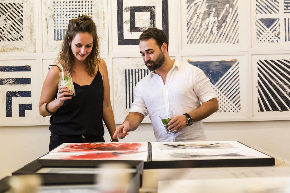 duas pessoas observando um quadro de arte, em Cuba.