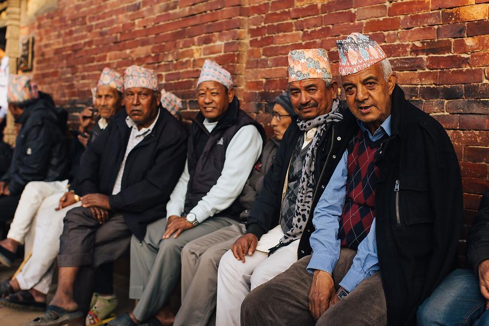 homens nepaleses sentados e olhando para a câmera