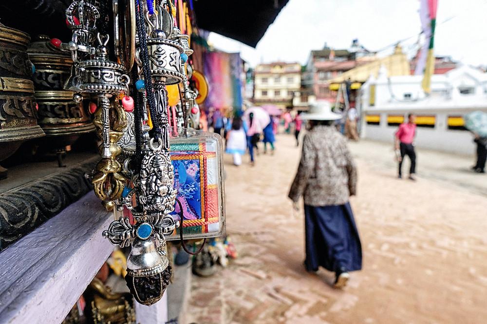 mulher andando pelas ruas do Nepal com objetos pendurados em tendas