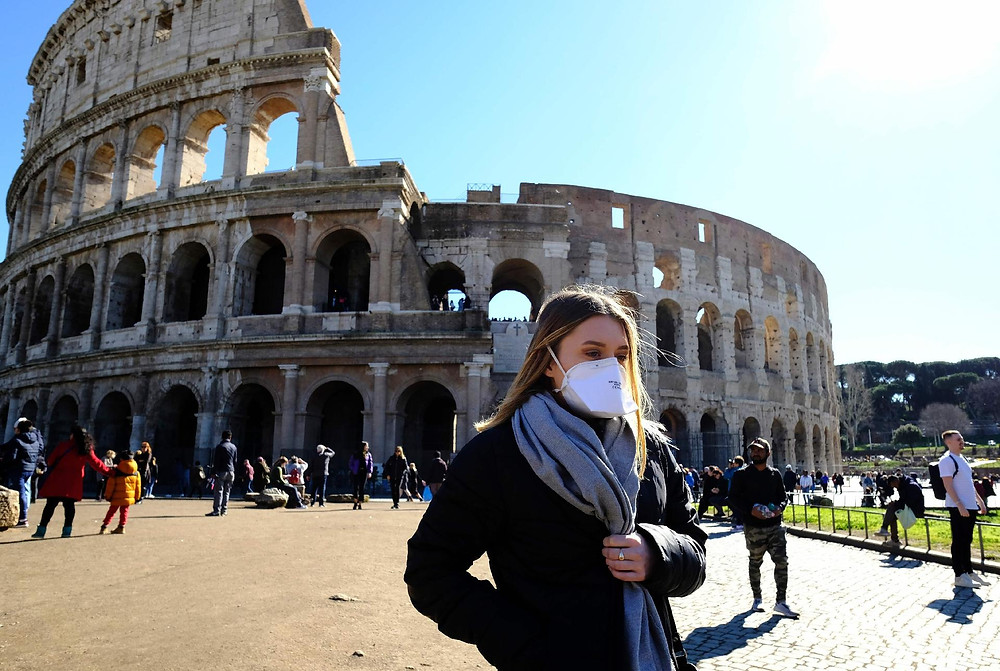 menina com uma máscara em frente ao Coliseu, na Itália
