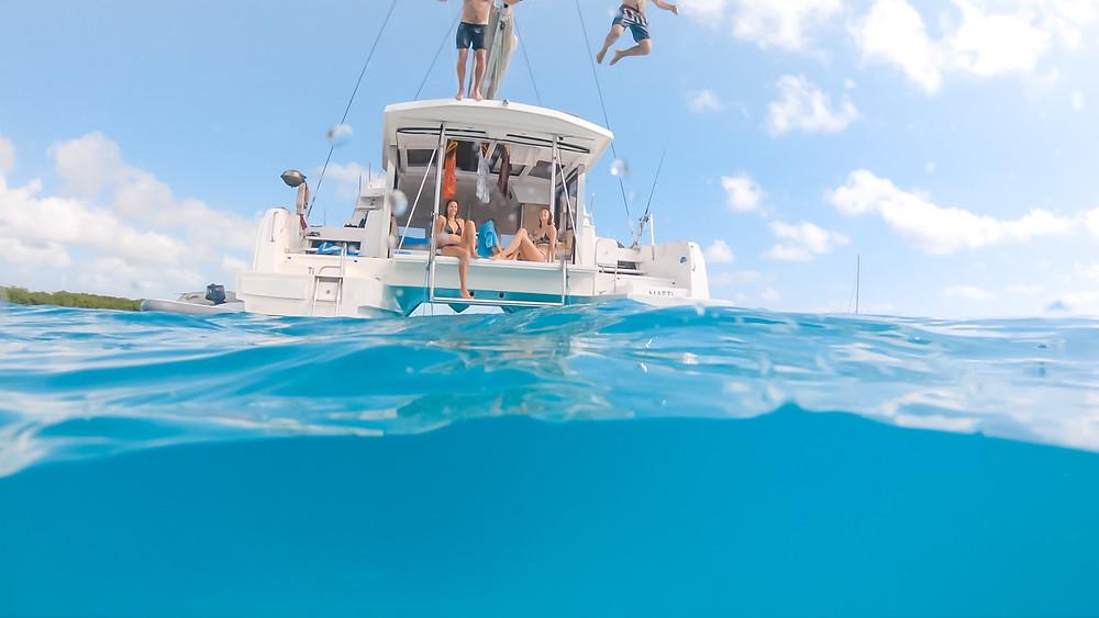 pessoas em um catamarã, em Cuba. Um menino está se jogando ao mar na embarcação.