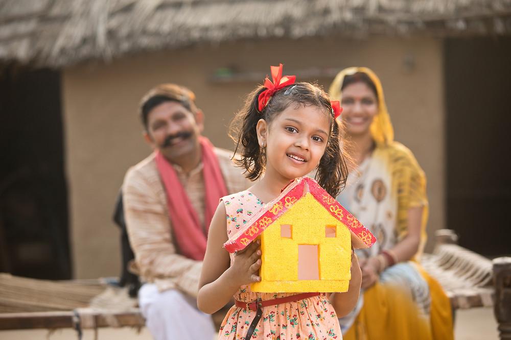 Uma criança segurando uma casa de papel, enquanto seus pais a observam no fundo