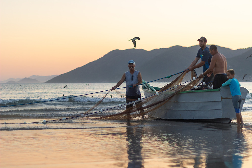 Uma praia no Brasil. Pescadores em um barco, com uma rede
