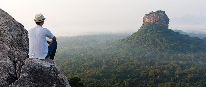 Homem de costas observando a pedra do leão ao fundo, no Sri Lanka