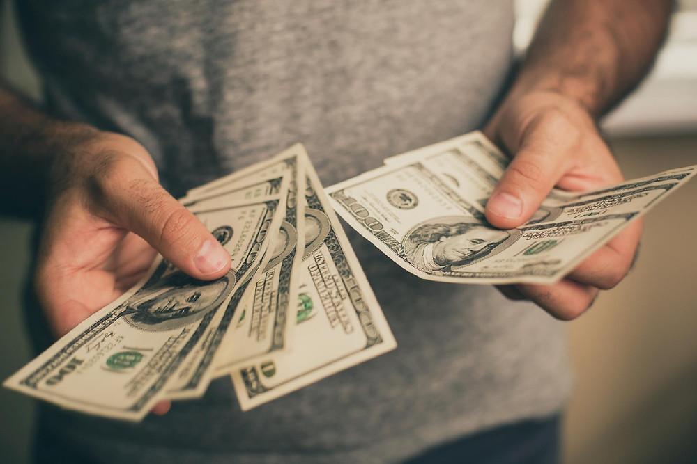 uma pessoa contando dólares