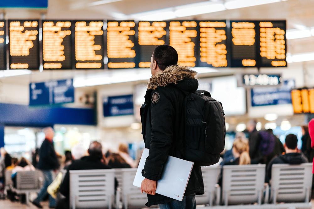 Um homem em um aeroporto, olhando o painel de viagens