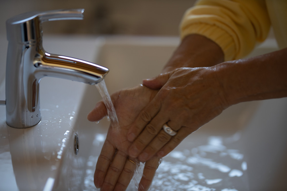 Uma mulher lavando as mãos na pia.
