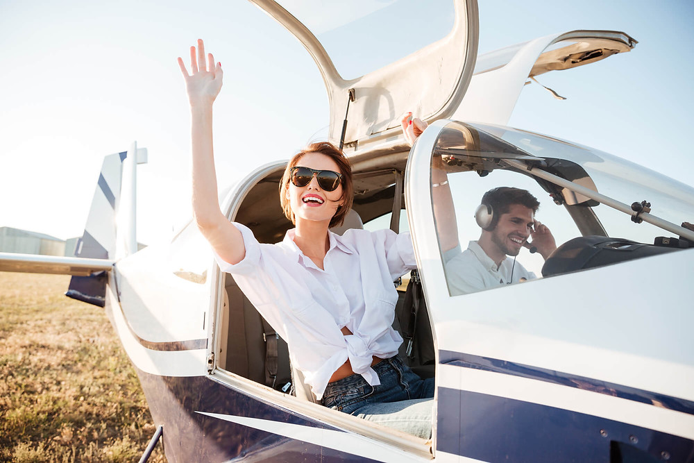 Uma mulher acenando dentro de um avião particular