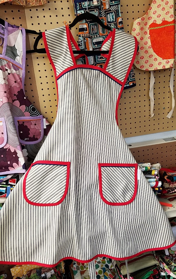 Custom apron from ticking fabric with red and navy trim