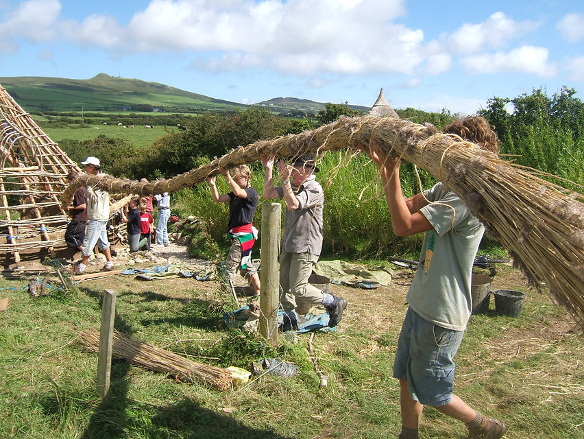 volunteers builing the new thatched roun