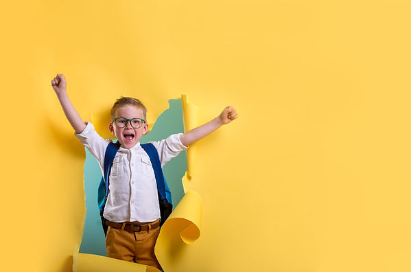 Child boy with book and bag breaking through yellow paper wall. Happy _smiling kid go back