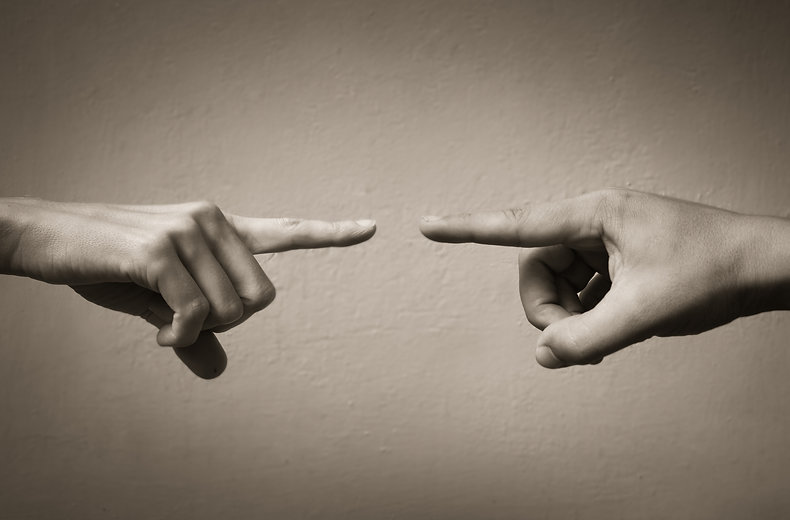 Hands pointing fingers at each other. Bl