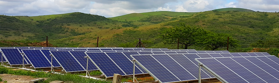 A picture of an array of solar panels set up as part of a greenfeild project