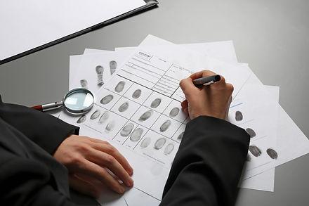Female criminalist filling fingerprints