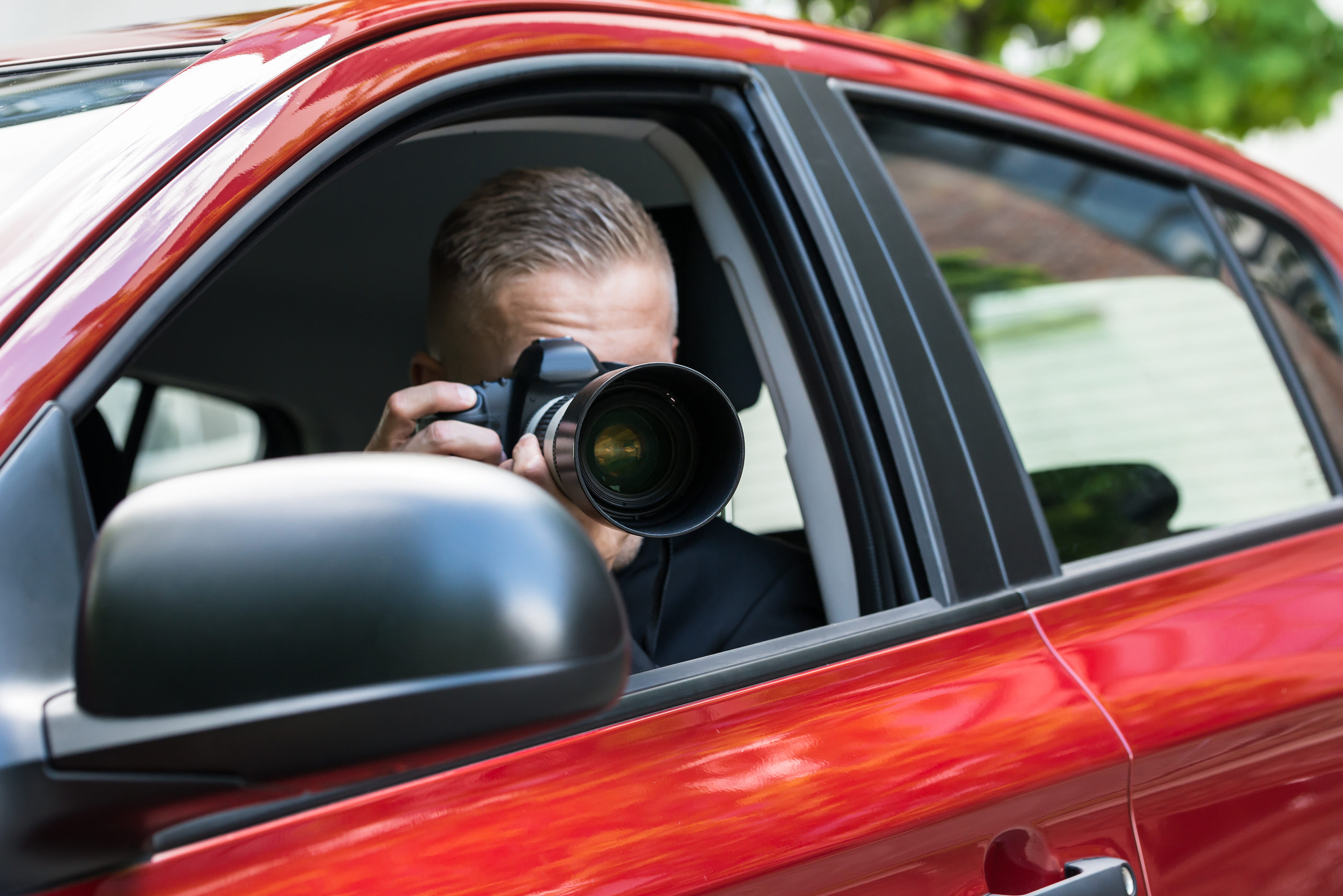 Man Photographing With Slr Camera From Car