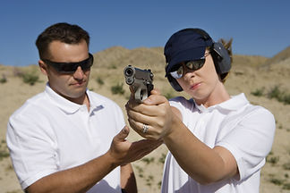 Trainer helping young woman to aim with