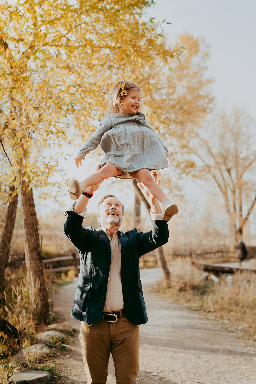 Father tossing child fall family photo session Jacksonville Florida with fall leaves