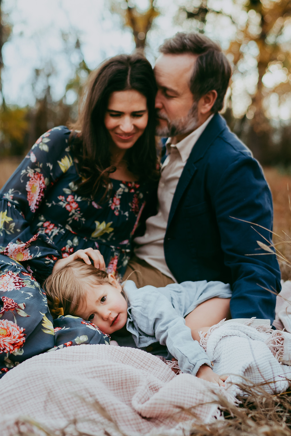 Fall family photo session with mother father and daughter in field in Jacksonville Florida