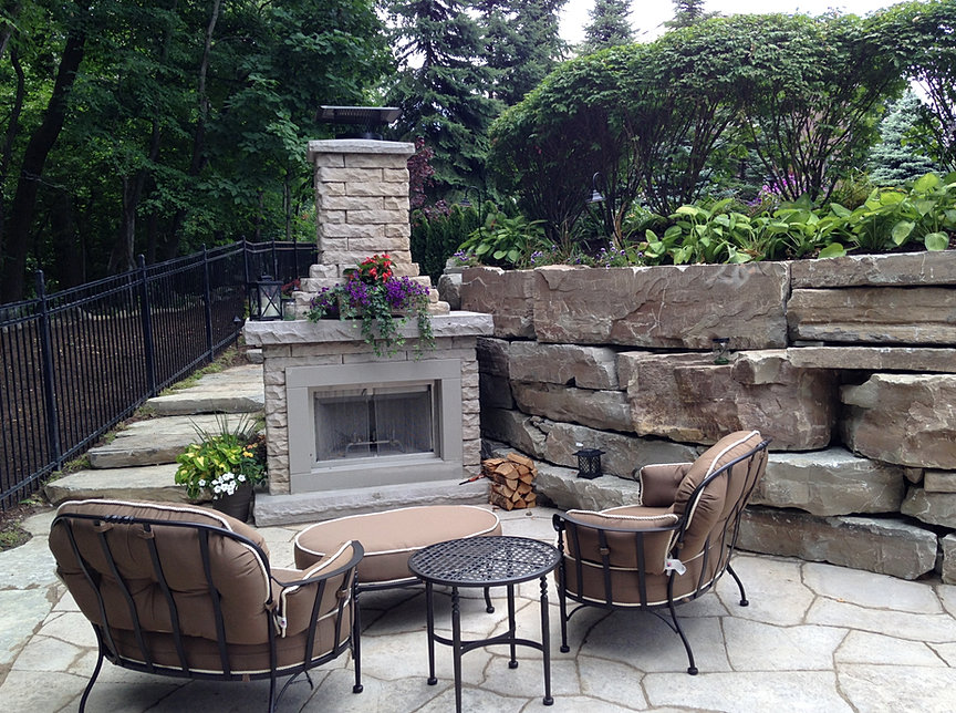 After: Complete. A Patio With A Fireplace And Rock Wall.
