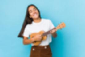 Young indian woman happy playing ukelele