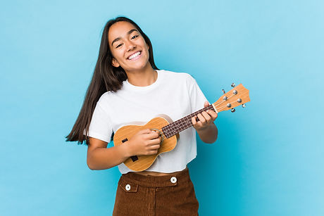Young indian woman happy playing ukelele