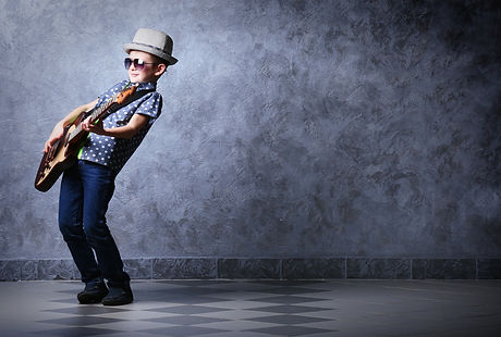 Little boy playing guitar on a grey wall