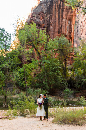 Elope southern utah - Temple of Sinawava wedding bride and groom stand in front of red rock wall in zion national park
