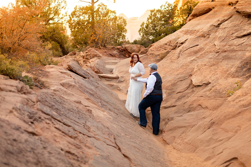 Elope Southern Utah - Zion canyon overlook elopement bride guides the groom along the trail in zion national park