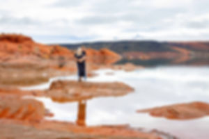 Elope Southern Utah Engagement photo in red rocks with glassy blue water surrounding th couple