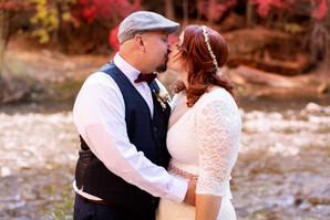 Elope Southern Utah - temple of sinawava wedding bride and groom share their first kiss in front of red, yellow, and green fall leaves in zion national park
