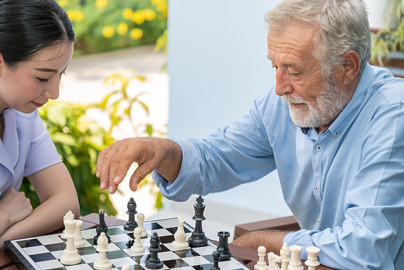 Elderly playing chess with nurse caregiv