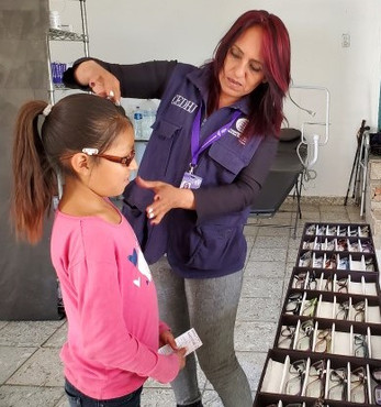 Anita helping young girl select glasses.