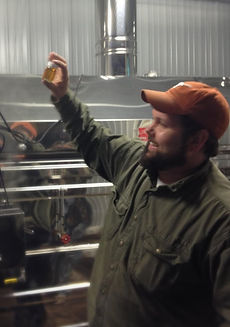 Head sugarmaker Greg Young checking the grade of the syrup coming off of the evaporator during maple sugar season.  It looks like a nice golden color and he is happy with that.  The evaporator is clean and ready for more production.