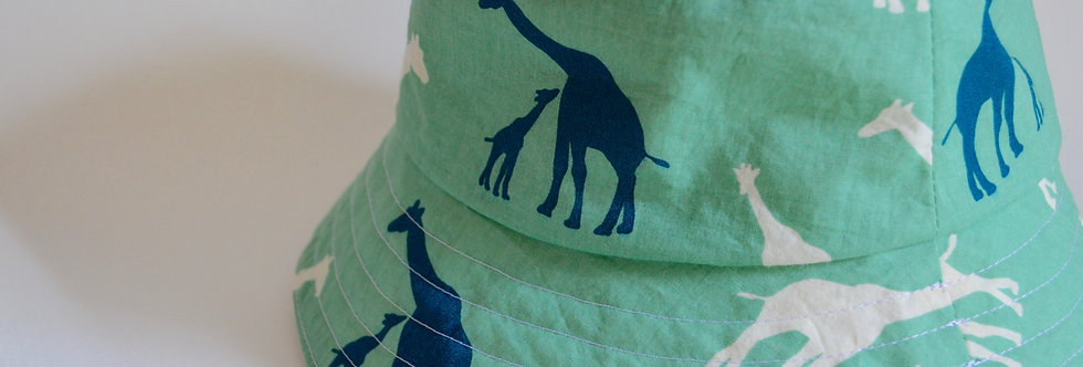 Reversible bucket hat for kids with giraffes on green organic cotton fabric