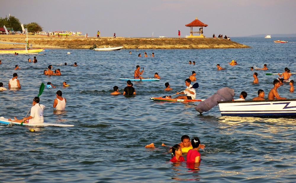 Local families swimming at Sanur beach